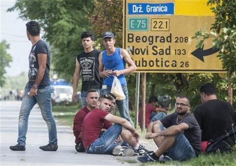 Refugees rest near the border station between Serbia and Hungary in Horgos, Serbia. (Sandor Ujvari/MTI via AP)