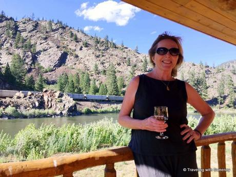 Sweeney enjoying a glass of wine on the porch of a cabin at Quinn's Hot Springs Resort in Paradise, Montana