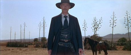 Both of Mortimer's belts - his trouser belt and his black gun belt - are seen as Manco directs the standoff against El Indio.