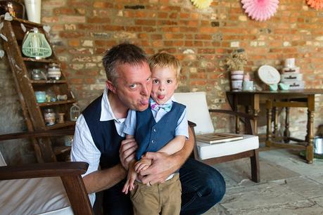 Canidid photographs at barmbyfiled barn wedding pageboy sticking tongue out