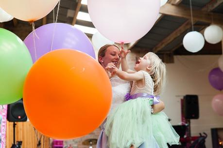 Canidid photographs at barmbyfiled barn wedding flowergirl with balloons