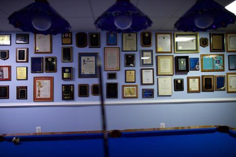 A wall covered with plaques, awards & testimonials to you-know-who in basement near a pool table
