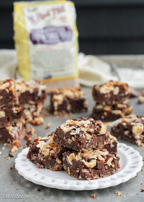These Chocolate Hazelnut Magic Bars are a new flavor twist on a classic cookie bar. The crust is kept naturally gluten-free with hazelnut flour. A gooey Nutella filling and topping made of chocolate chips, flaked coconut, and hazelnuts takes these bars over the top!