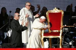 Pope Francis kneels
