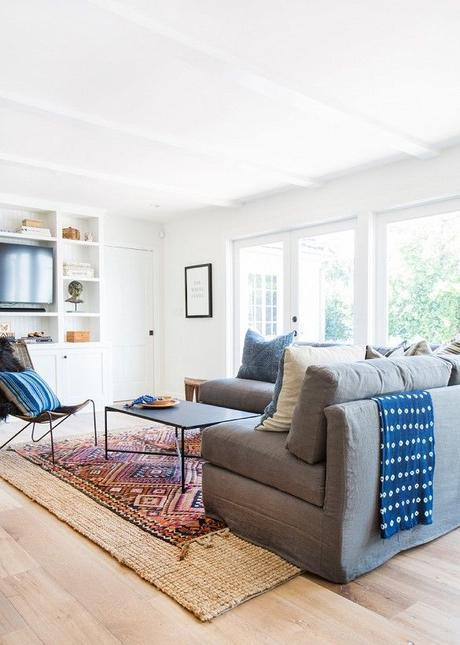 Cozy white living space with sectional and blue throw: