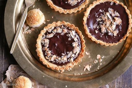 These Chocolate Ganache Tarts with Coconut Macaroon Crust are Paleo, gluten-free + refined sugar free, but you'd never guess from the decadent vegan chocolate ganache or sweet and chewy crust.