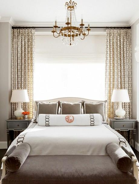 Big open window, white lamps, grey furniture, small chandelier and monogrammed bedding:
