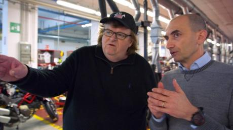 This image provided by Dog Eat Dog Films shows director Michael Moore, left, and Claudio Domenicali, CEO of Ducati, in a scene from his documentary,