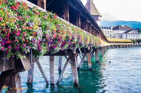 Colorful flowers line Kapellbrücke covered bridge, Lucerne.