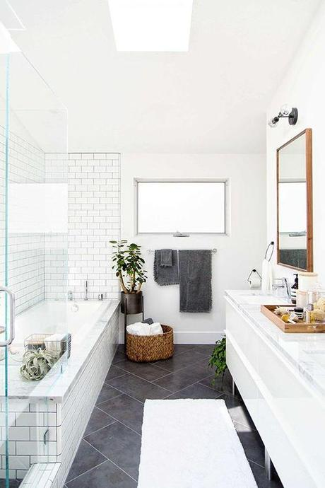 Love this large charcoal gray diagonal tiles on the floor paired with the white subway tiles and gray grout in the shower. Such a fresh look with the modern white cabinets and wood mirror!: