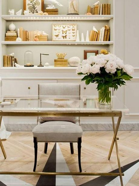 Glass and golden desk, gray chair, decorated shelves, white flowers: