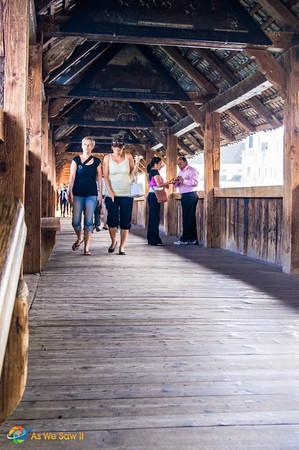 People crossing Lucerne's medieval wooden bridge
