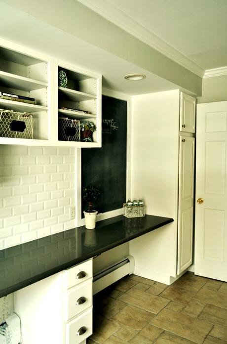 chalkboard in laundryroom with white cabinetry