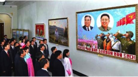DPRK citizens look at paintings and posters that are part of an art exhibition which opened at the Korea Art Gallery in Pyongyang on May 2, 2016 as part of celebrations for the convocation of the 7th Party Congress (Photo: Rodong Sinmun).