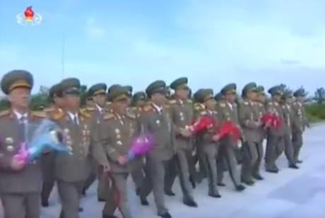 7th Party Congress participants bring floral bouquets to the stand at the entrance to Revolutionary Martyrs' Cemetery on May 4, 2016 (Photo: Korean Central TV).