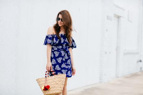 Amy Havins wears a blue off the shoulder dress with flat sandals.