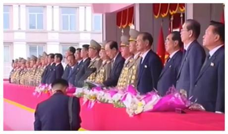 WPK Political Bureau Presidium Member and SPA Presidium President Kim Yong Nam speaks during a May 10, 2016 rally and parade held to celebrate the 7th Party Congress while a KCNA photographer checks his shot (Photo: Korean Central TV).