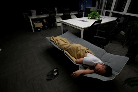 Ma Zhenguo, a systems engineer at RenRen Credit Management Co., sleeps on a camp bed at the office after finishing work in the early morning.