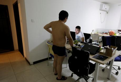 Some offices are run out of apartments, such as N-Wei (Beijing) Technology Co. Ltd. Here, a programmer chats with his colleague before he heads off to bed.