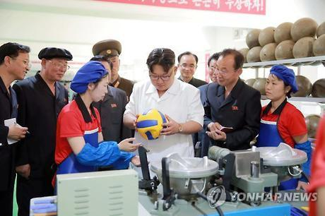 Kim Jong Un inspects a volleyball during his visit to the Pyongyang Sports Apparatus Factory (Photo: KCNA-Yonhap).