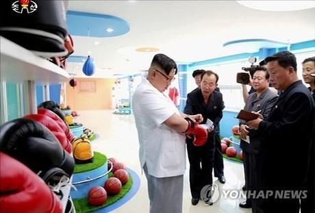 Kim Jong Un tries on a boxing glove looking at productions of the Pyongyang Sports Apparatus Factory (Photo: KCTV-Yonhap).