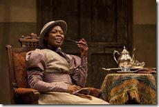 Prudence (Zainab Jah) enjoying a pipe and cup of tea at Chilford's house in the world-premiere co-production of The Convert by Danai Gurira, directed by Emily Mann.