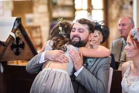 groom hugging a flower girl