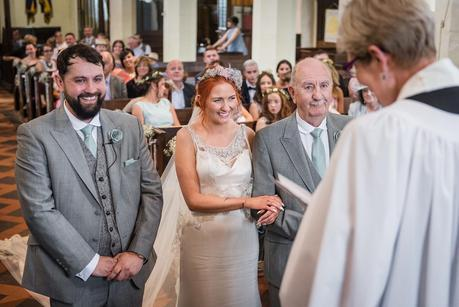 groom and bride and her father in a church