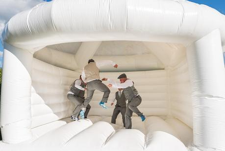 groom on bouncy castle at a rustic wedding