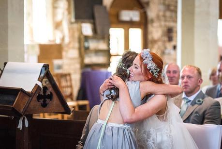 bride hugging a flower girl