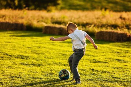 little boy kicking a ball at a wedding