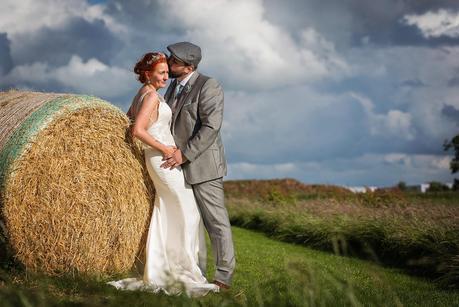 groom kissing brides head against hay bails