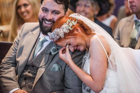 bride laughing on the grooms shoulder