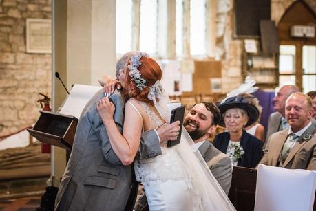 bride hugging her father after his wedding reading