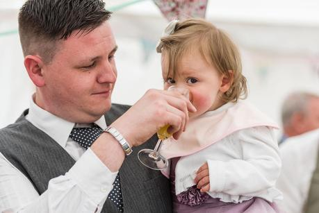 a little girl having a drink at a wedding