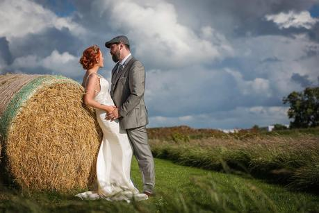 bride and groom leaning against hay bails