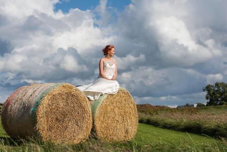 bride sitting on hay bails at a rustic wedding