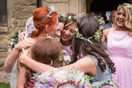 a bride in a group hug with her bridesmaids