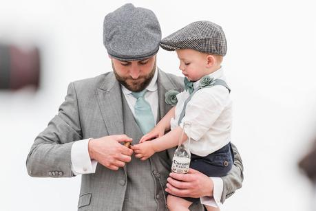 an usher holding his son at a summer wedding