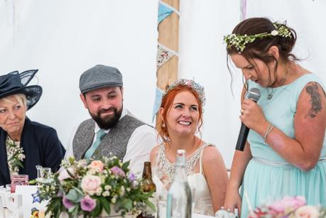 bride smiling at her sisters wedding speech