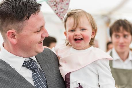 a little girl smiling with her father at a wedding