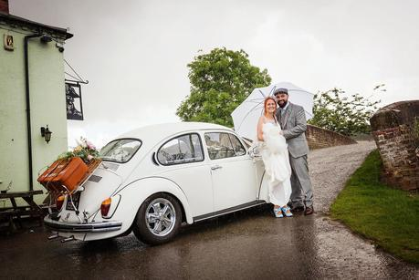 bride and groom in the rain by their wedding car