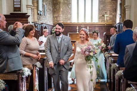bride and groom walking out of hillmorton church
