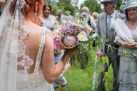 a bride holding her flowers outside the church