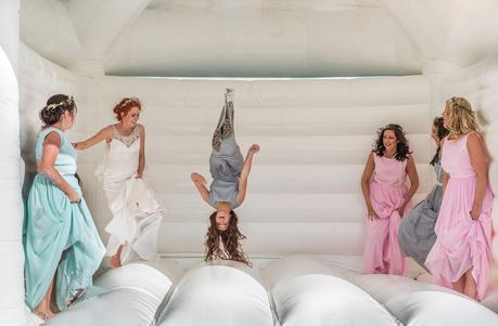 documentary photography - bridesmaid upside down on bouncy castle