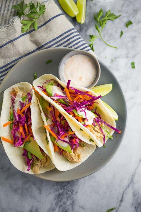 These Sweet Chili Chicken Tacos are made with slow cooker sweet chili chicken and topped with yogurt sauce. This dinner is ready in just 15 minutes!