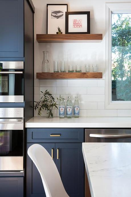 Blue Cabinetry And White Quartz Countertop And Floating Wood Shelves