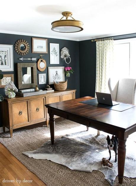 Home office with charcoal gray walls and eclectic gallery wall above a credenza: