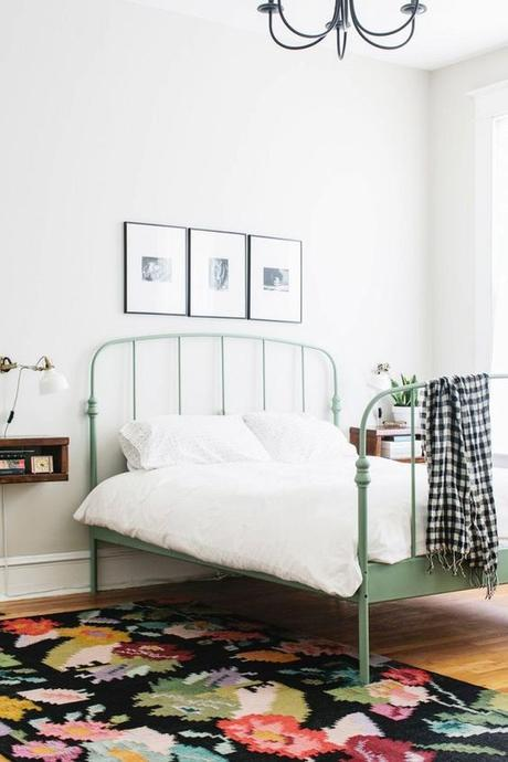 Feminine yet minimal bedroom with a floral area rug, a white sconce, and a green metal bed frame:
