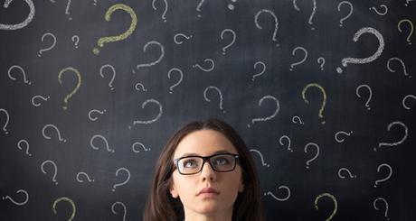 Chalk question marks above businesswoman at blackboard